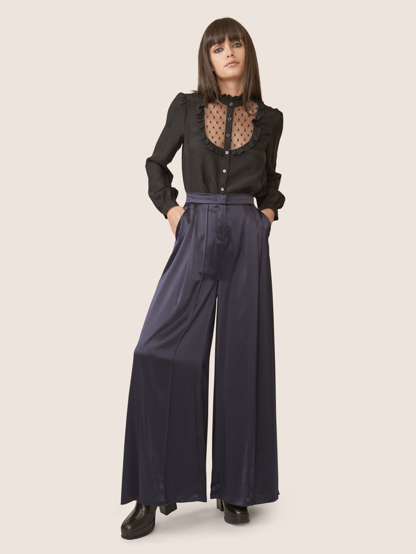 Front view of high waisted satin wide leg pants with side pockets.
