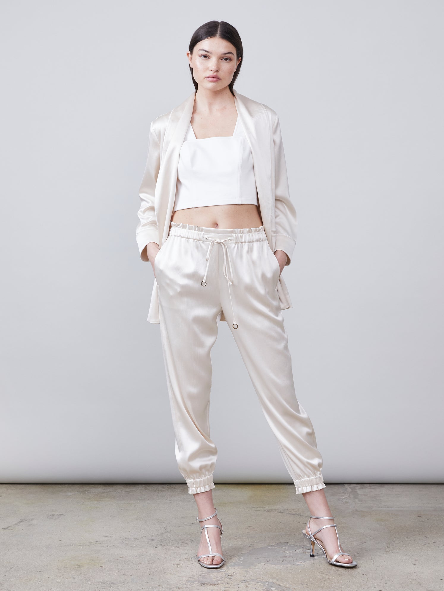 Front view of the Trinity Sustainable Satin Track Pant paired with the Harper Sustainable Satin Jacket in eggshell