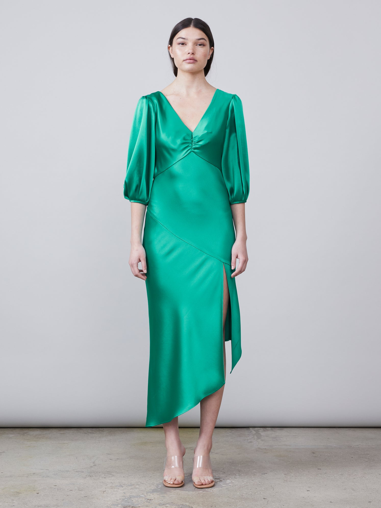 Front view of the Louise Deep-V Dress in jade featuring an asymmetrical hemline, front slit and puff sleeve