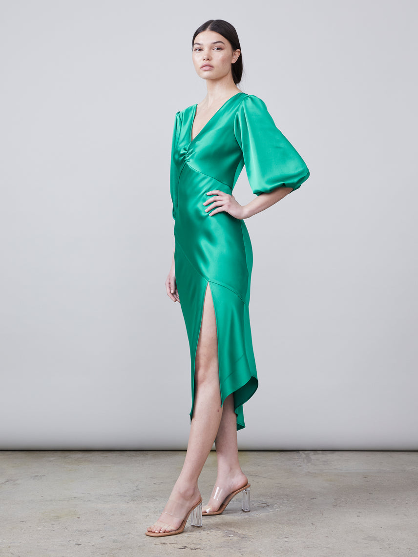 3/4 view of the Louise Deep-V Dress in jade featuring an asymmetrical hemline, front slit and puff sleeve