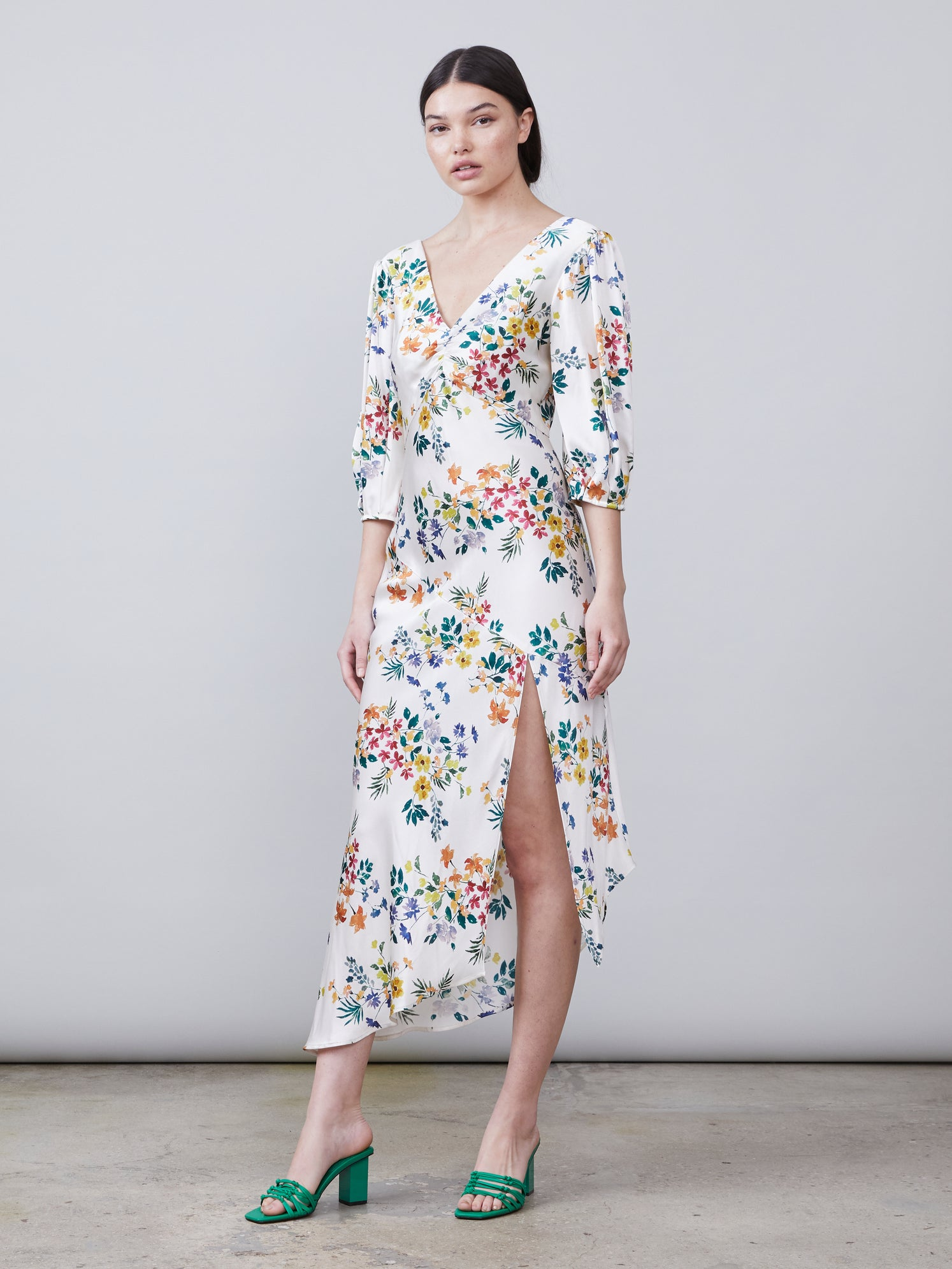 3/4 view of Louise Deep-V Dress in multi color floral print fabric featuring asymmetrical hemline, front leg slit and puff sleeves