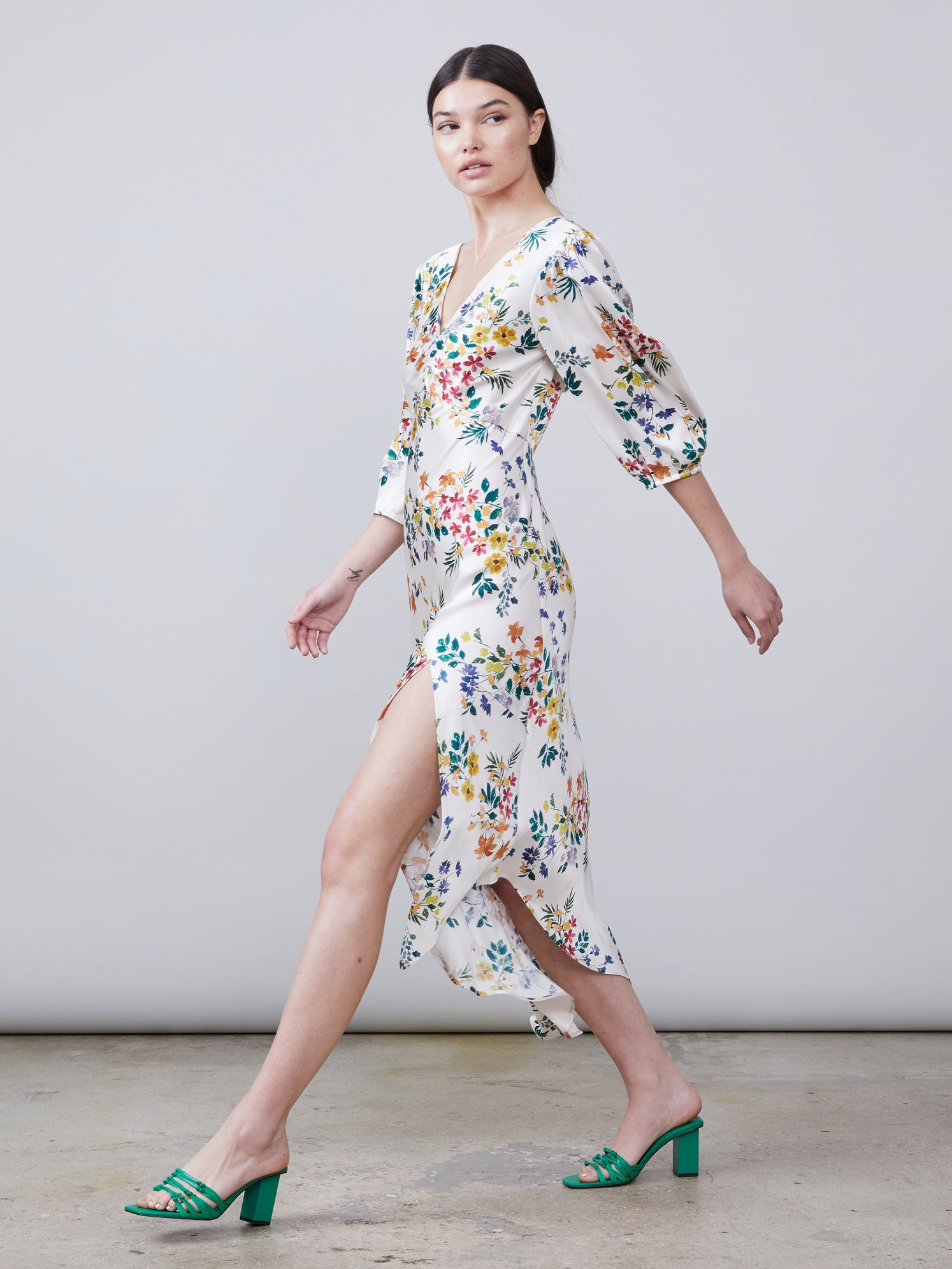 Side view of Louise Deep-V Dress in multi color floral print fabric featuring asymmetrical hemline, front leg slit and puff sleeves