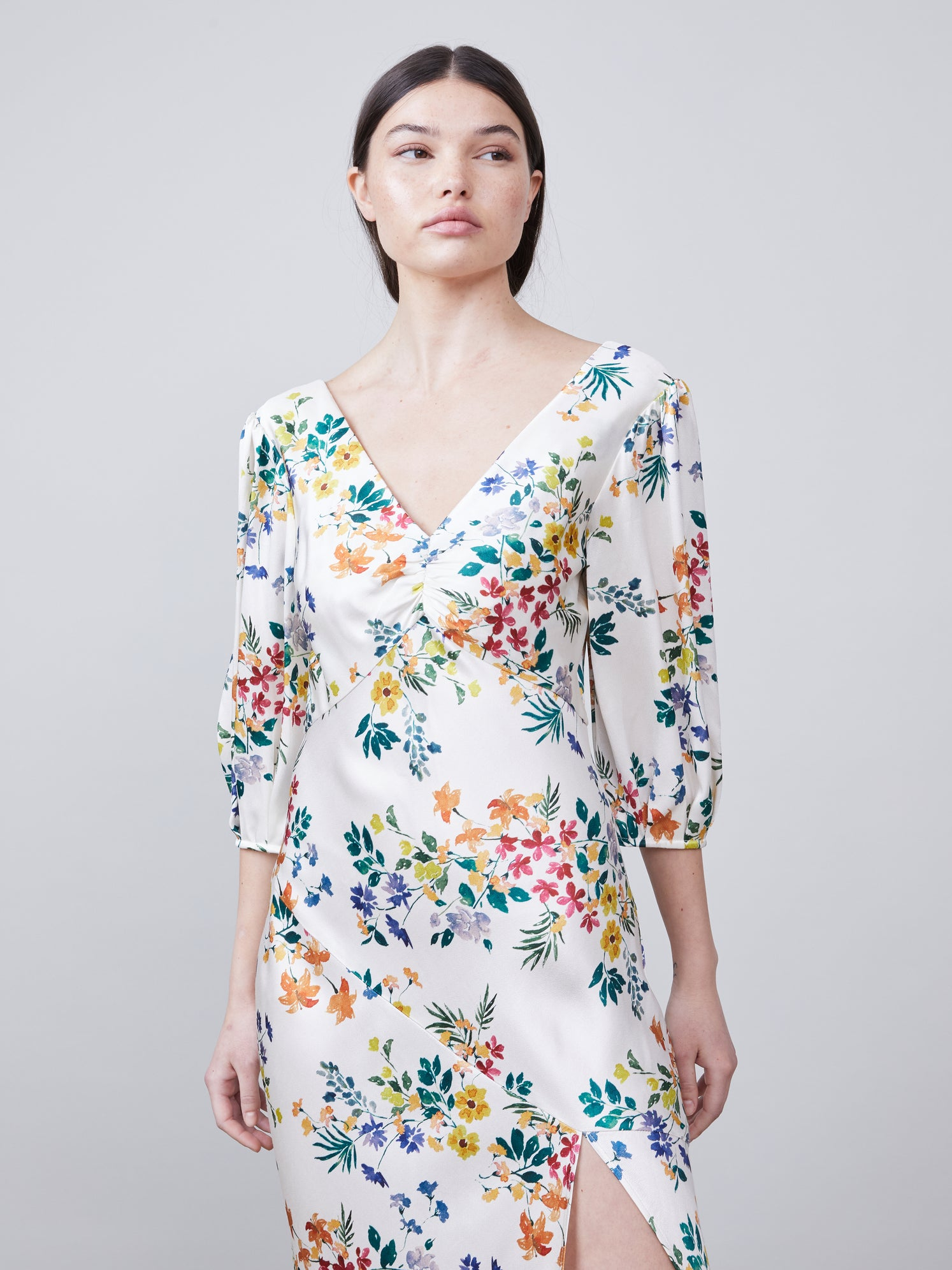 Close up view of Louise Deep-V Dress in multi color floral print fabric featuring asymmetrical hemline, front leg slit and puff sleeves