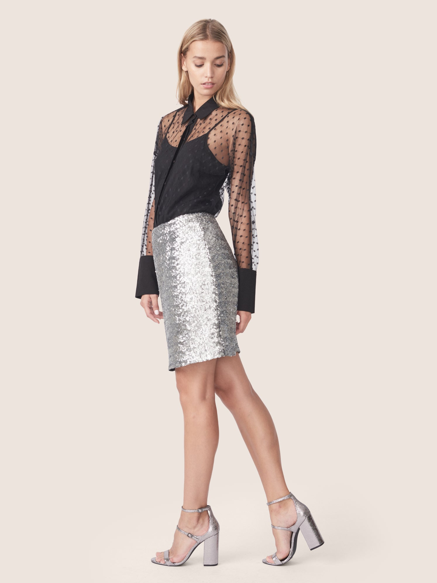 Side full body view of silver sequin mini skirt