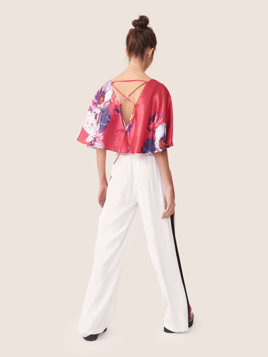 Floral print cropped blouse with layered capelet overlay and exposed cross tie back