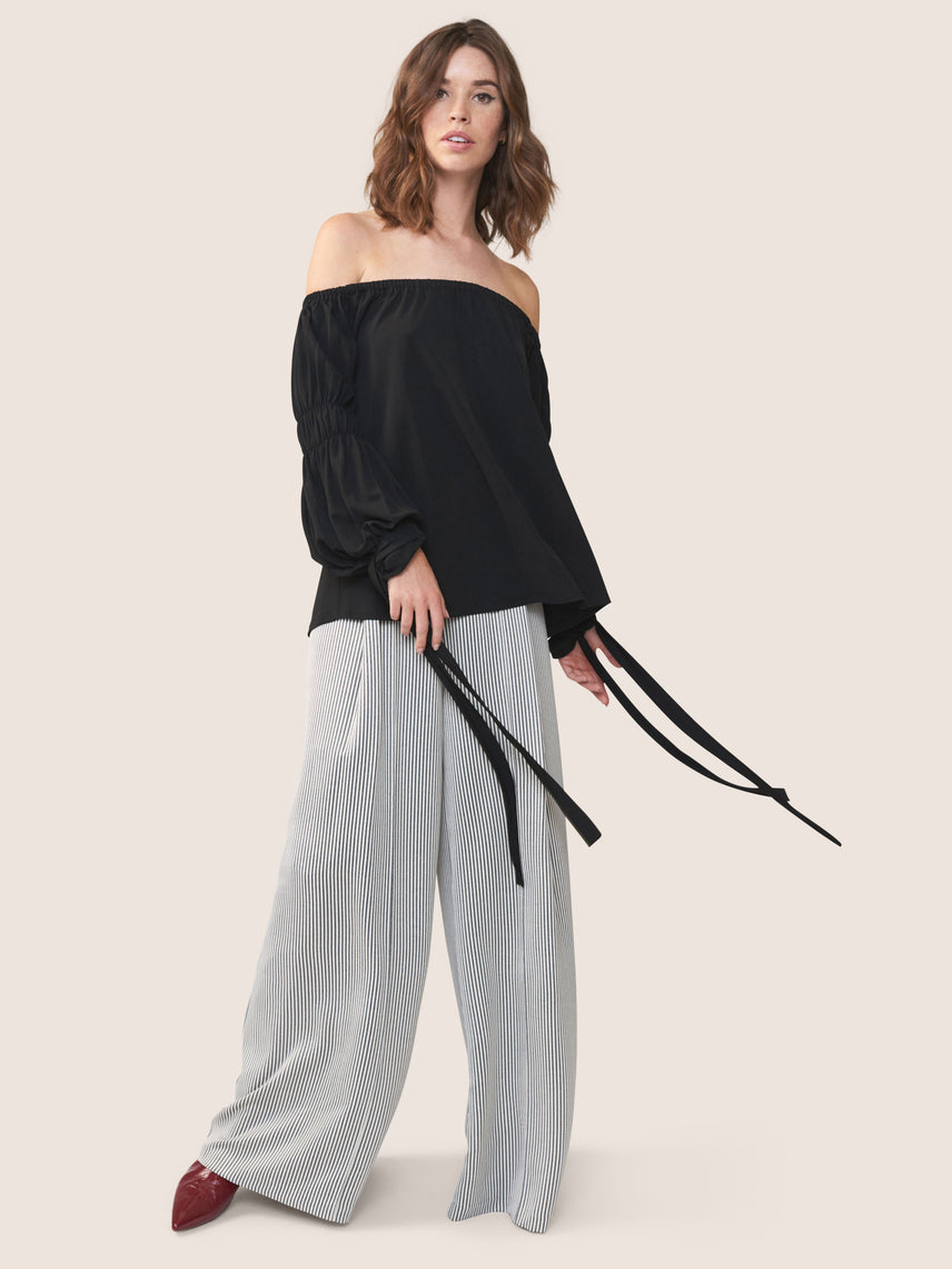 Black shirred off-shoulder blouse with elasticized top edge and statement removable ties at the wrist