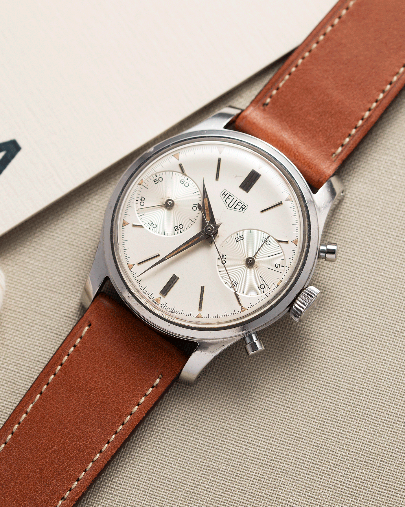 Brand: Heuer Year: 1950's Reference Number: 404 Material: Stainless Steel Movement: Valjoux 23 Case Diameter: 34mm Lug Width: 18mm Bracelet/Strap: Nostime Gold Tan Barenia Smooth Calf