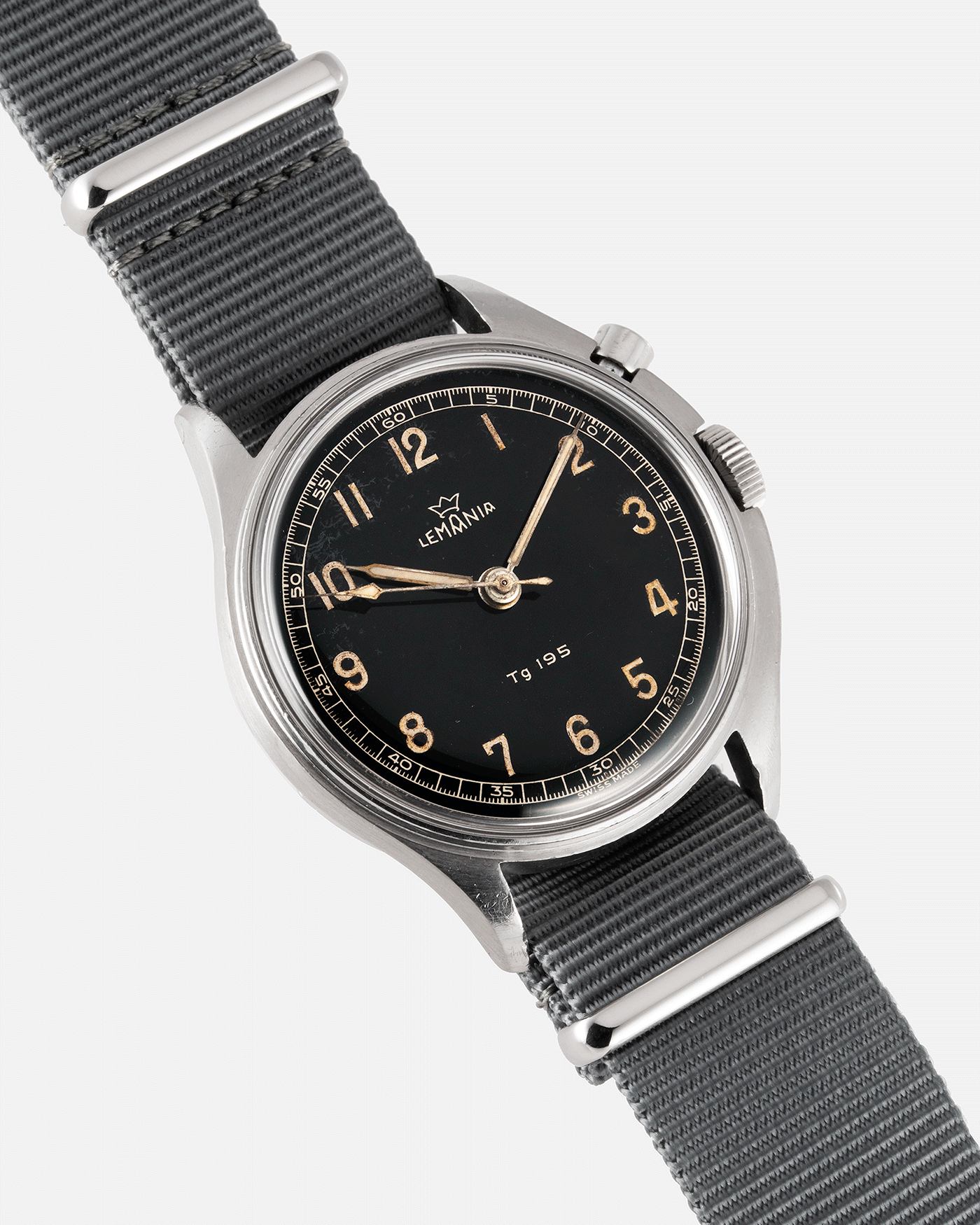 Brand: Lemania Year: 1957 Model: TG 195 Material: Stainless Steel Movement: Cal. 2225 Case Diameter: 40mm Lug Width: 20mm Bracelet/Strap: Grey NATO Strap