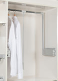 Starax pull and lift closet rod mechanism with handle to easily reach clothes in higher to reach places. Image shows mechanism in the closet in the lift or up position.