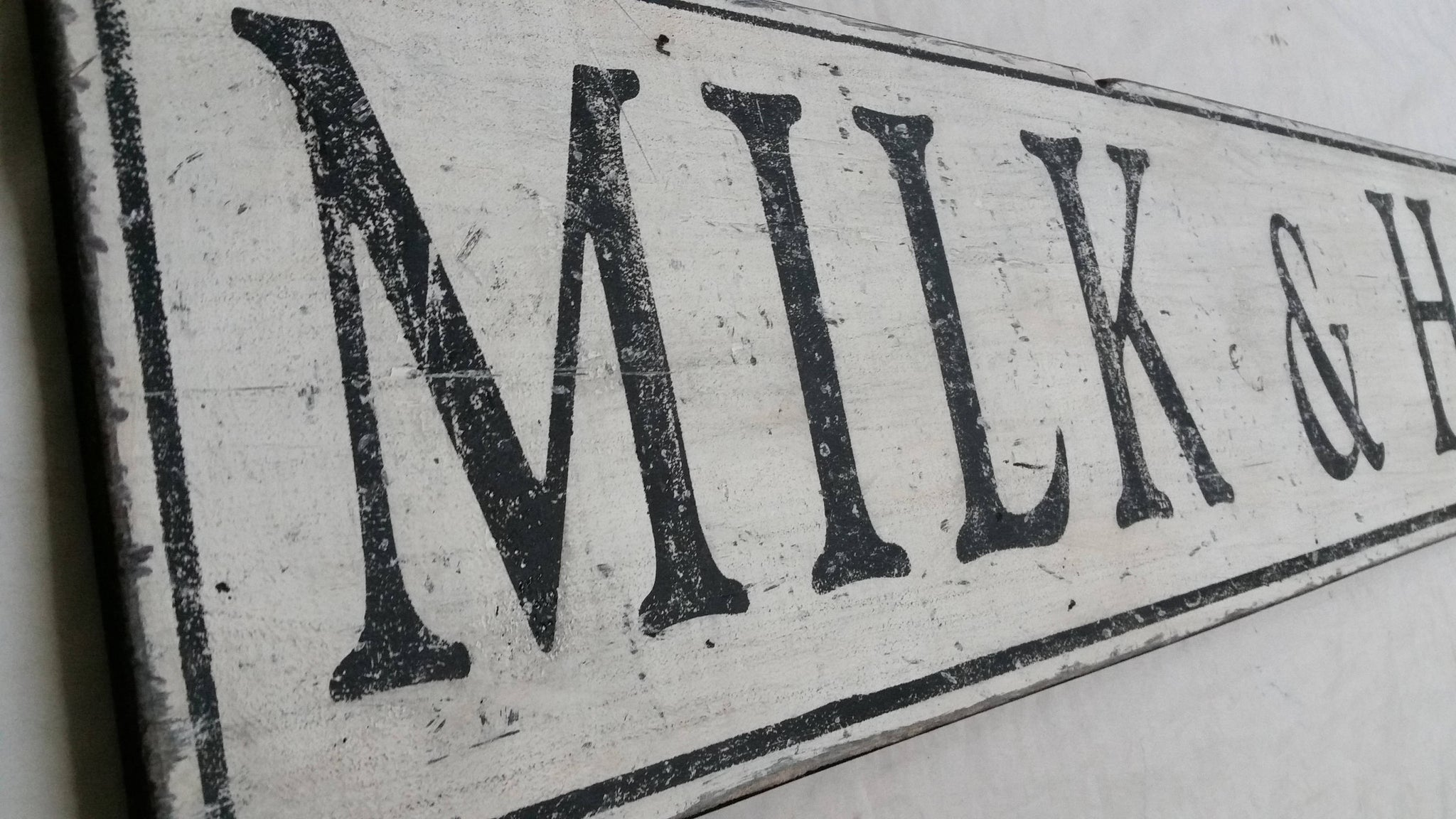 Milk and Honey sign distressing close up