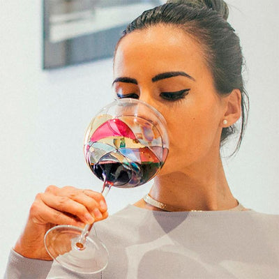 Luxury hand-painted tall wine glass inspired by the designs of Antoni Gaudi and Sagrada Familia. Woman drinking red wine from a full stemmed wine glass. Cornet Barcelona