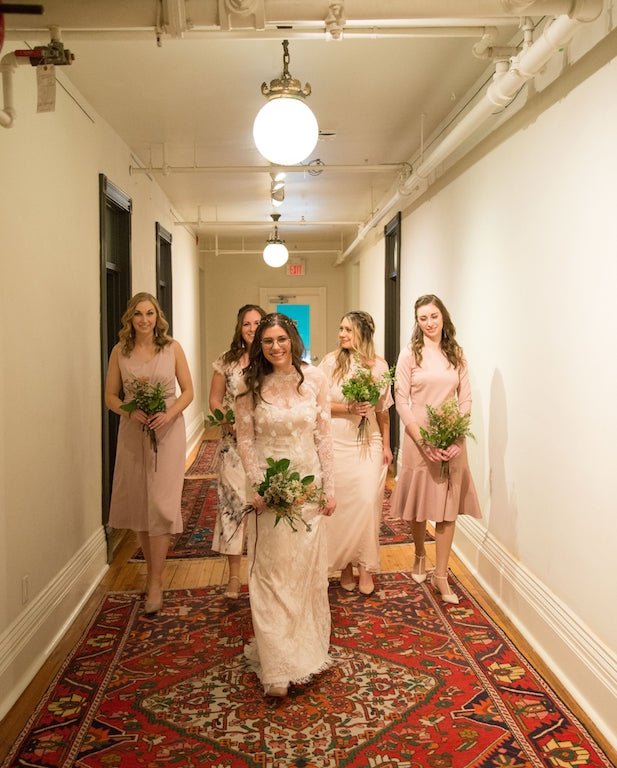A bride and her bridal party heading out to walk down the aisle.