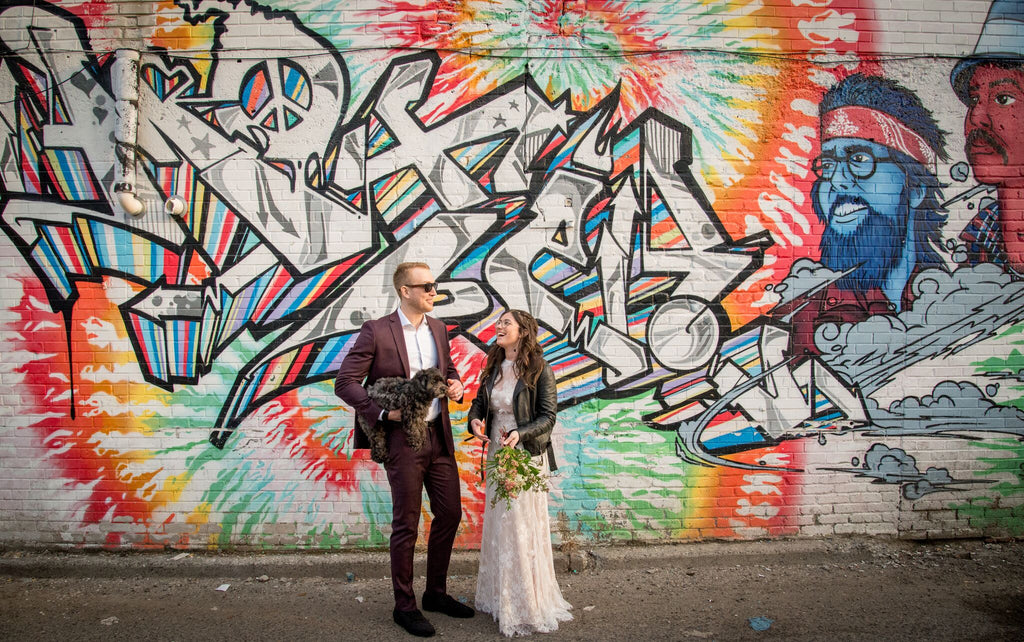 Toronto newlyweds standing in front of beautiful graffiti in an alley off Queen West in Toronto.