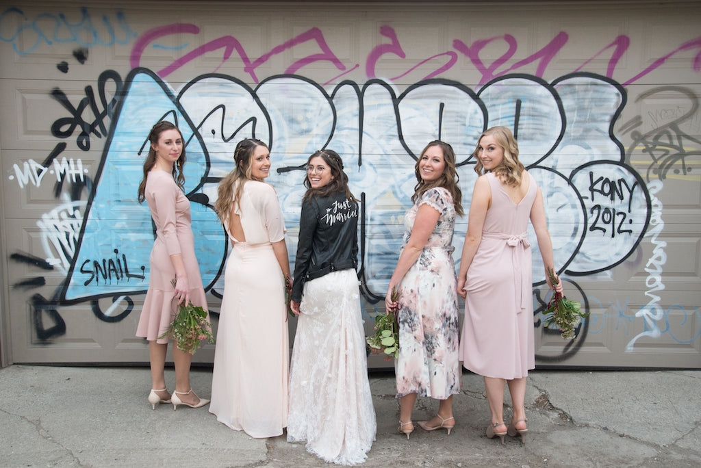 A bride and her bridesmaids pose for a photo in front of some graffiti.