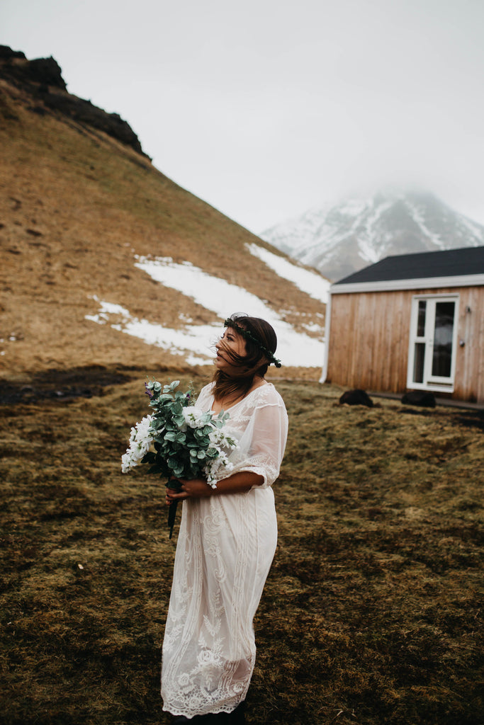 A bride wearing a lace wedding dress with a flower crown in Iceland.