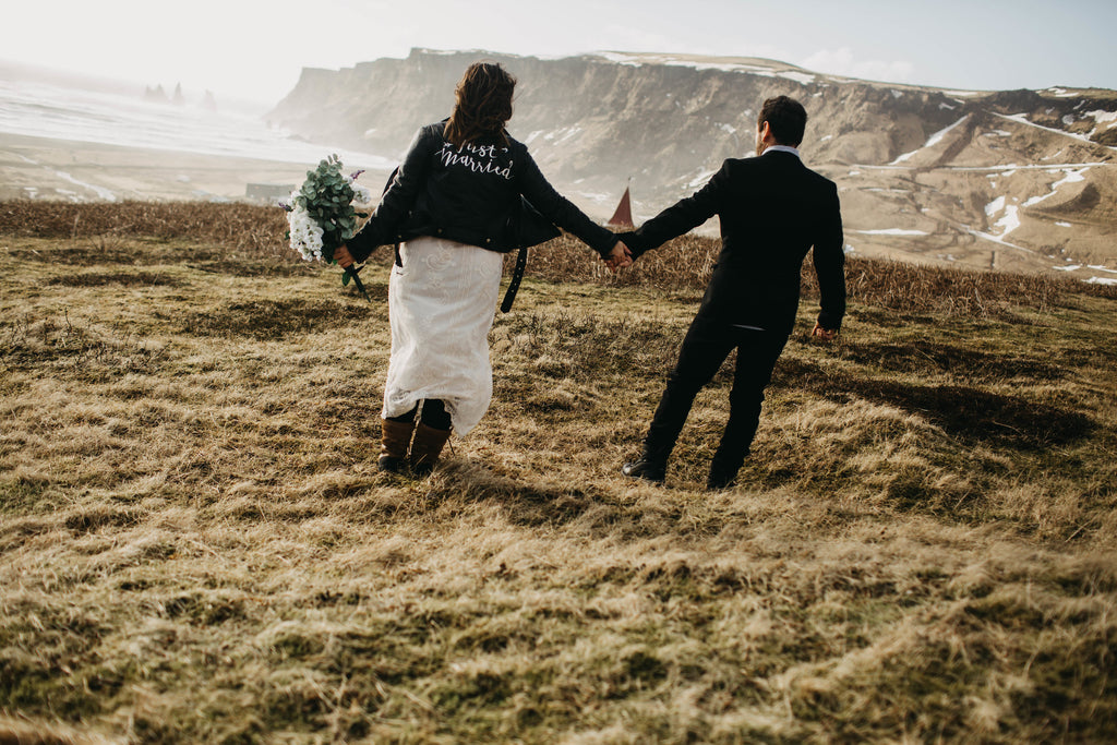 A newlywed couple frolics in a field in Iceland featuring #TheJustMarriedJacket.