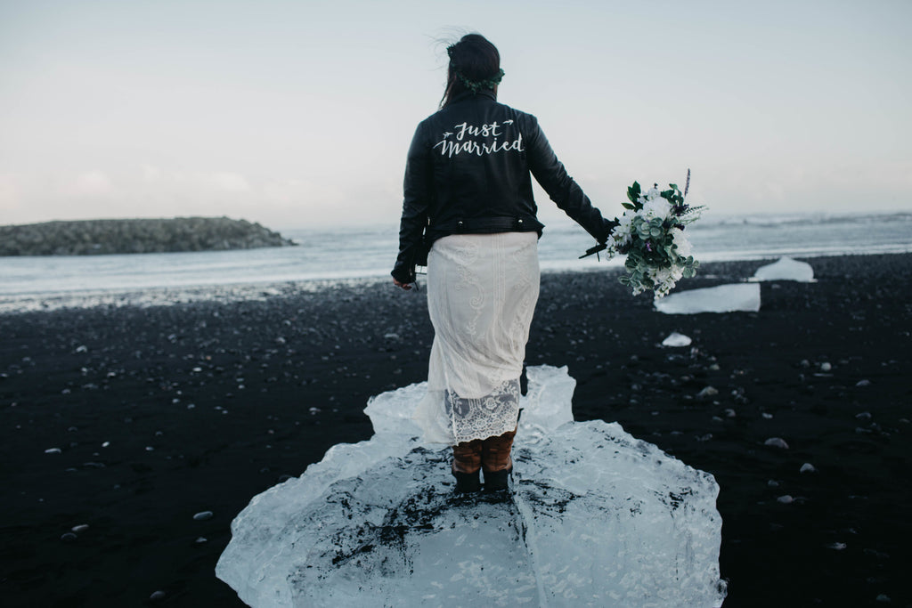 A bride shows off #TheJustMarriedJacket in front of a scenic beach in Iceland.