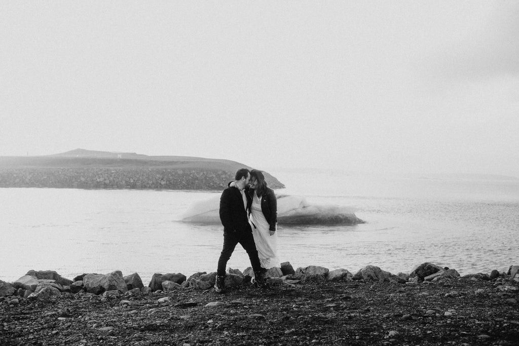 A happy couple in front of a beautiful beach in Iceland.