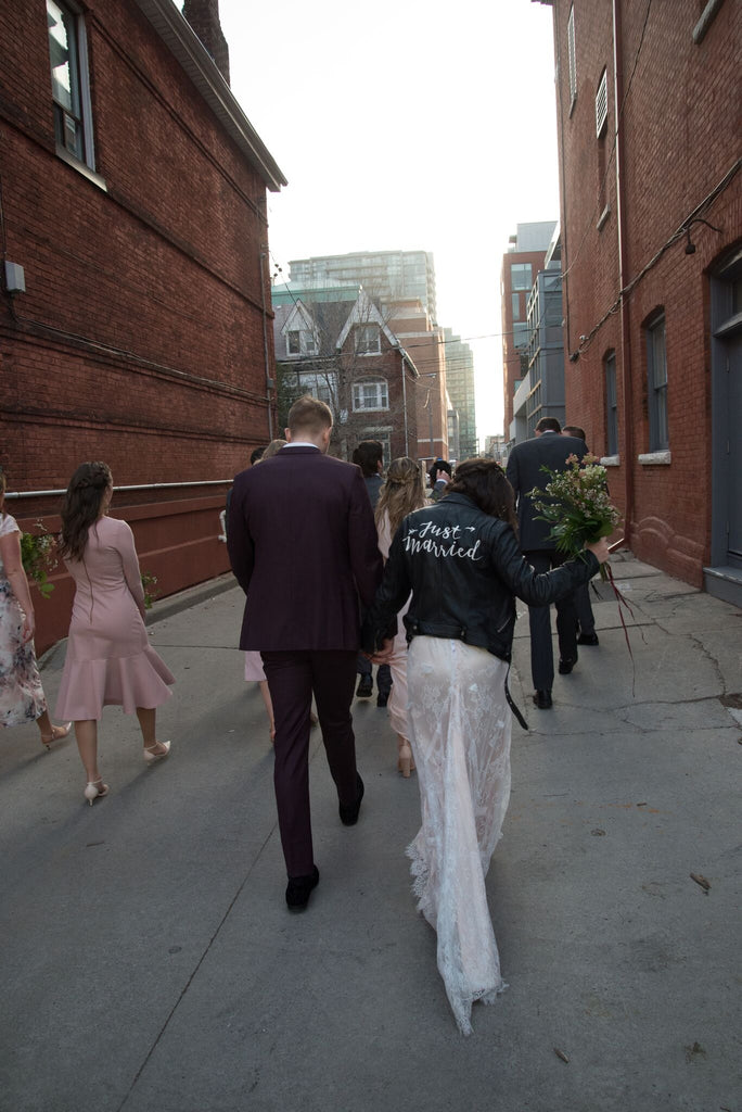 A bride sports her Just Married Jacket as her and her new husband walk down the road.