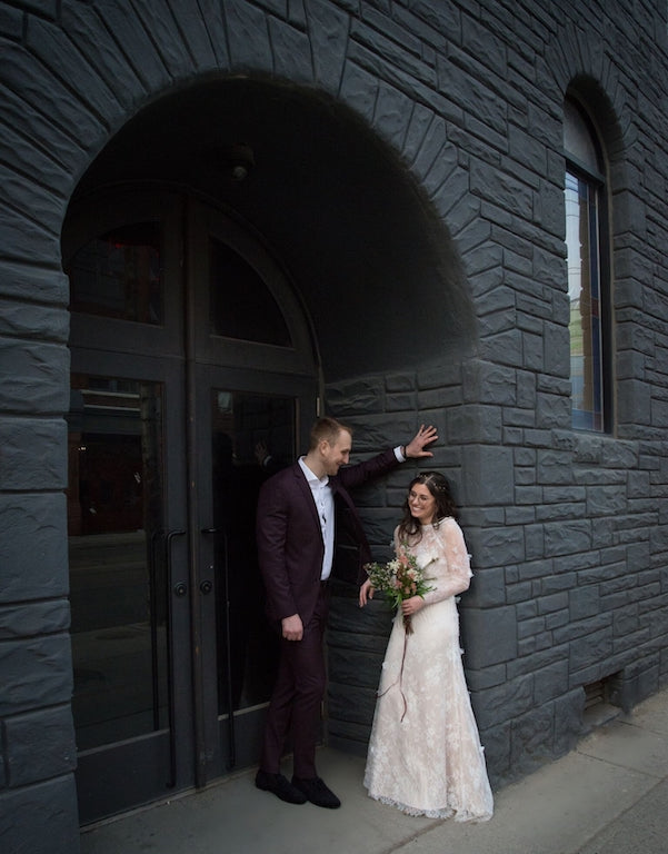 A bride and groom pose for a photo in a moody doorway.