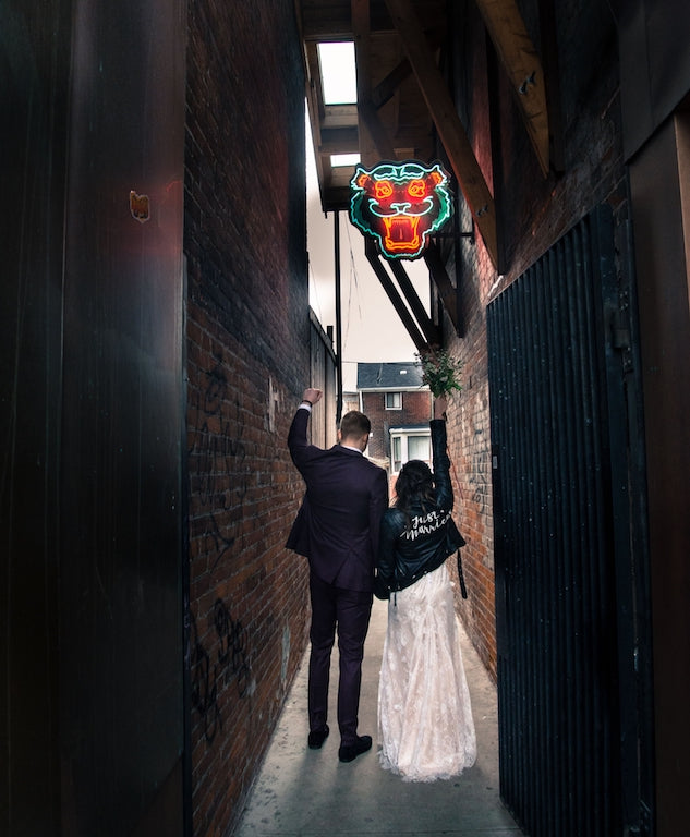 A newlywed couple walk to a restaurant for their reception.