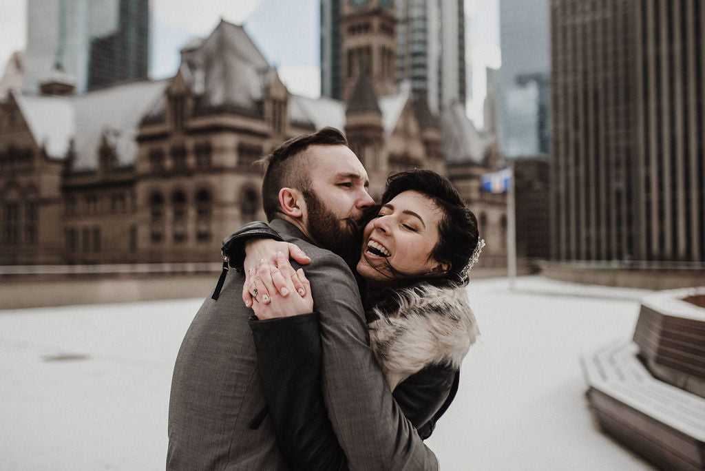 A happy newlywed couple hugs and kisses after exchanging vows at Toronto's City Hall.