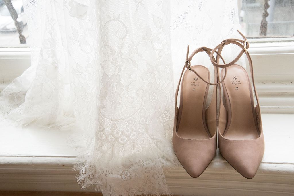 A bride's beige wedding shoes and wedding dress.