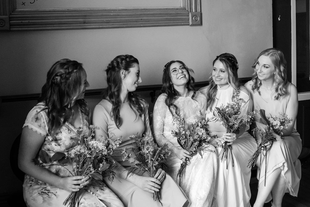 A bridal party sitting down and laughing together.