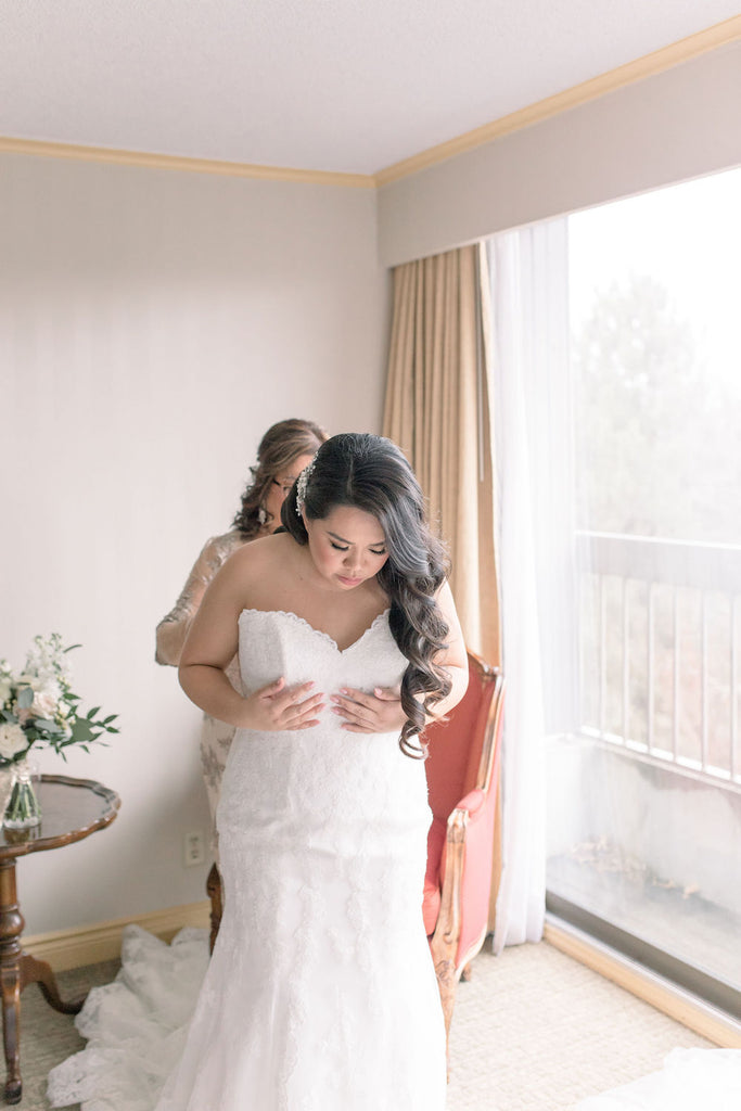 A bride gets ready with her mom who helps her put on her wedding dress.