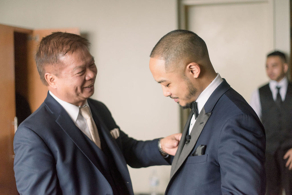 A groom gets ready with the help of his dad.