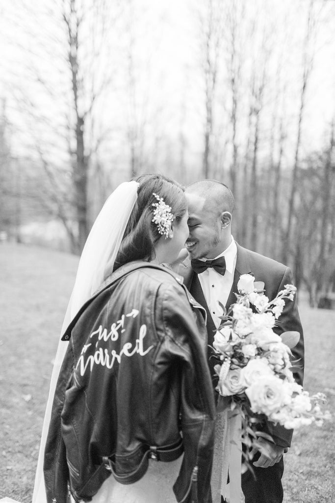 A bride and groom share a romantic moment. The bride is wearing #TheJustMarriedJacket.