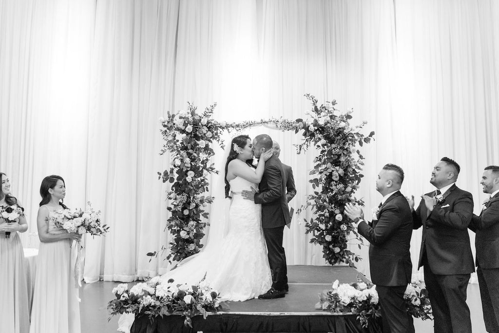 A happy couple kisses after saying 'I do' at the altar.