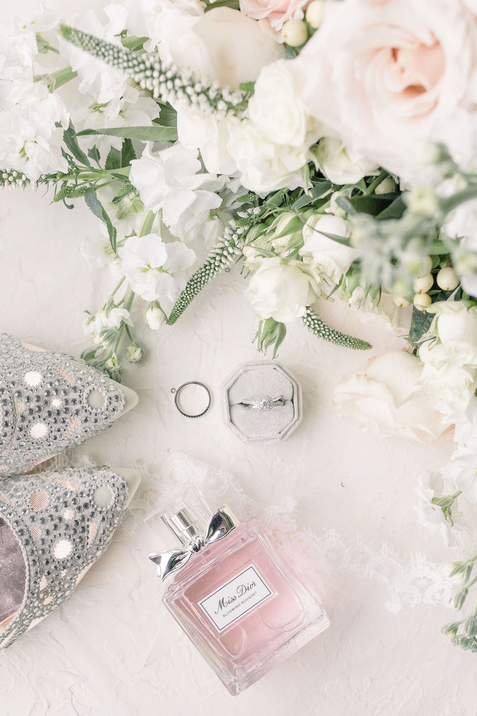 A bride's shoes, bouquet, perfume, and rings in a flatlay.