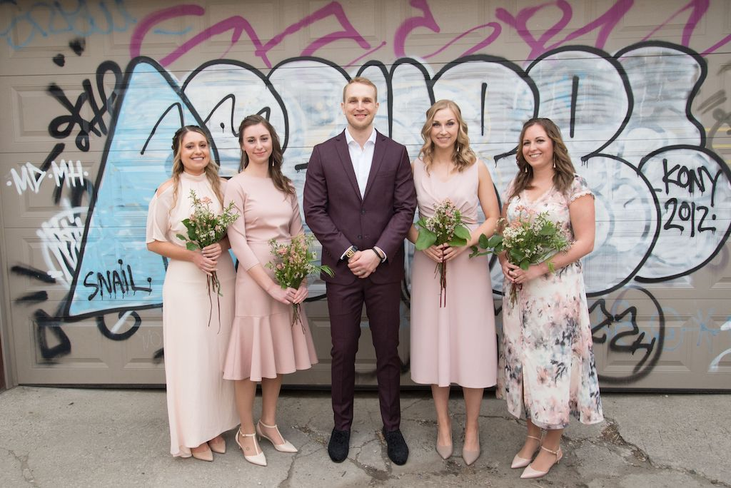 The bridesmaids pose for a photo with the groom.