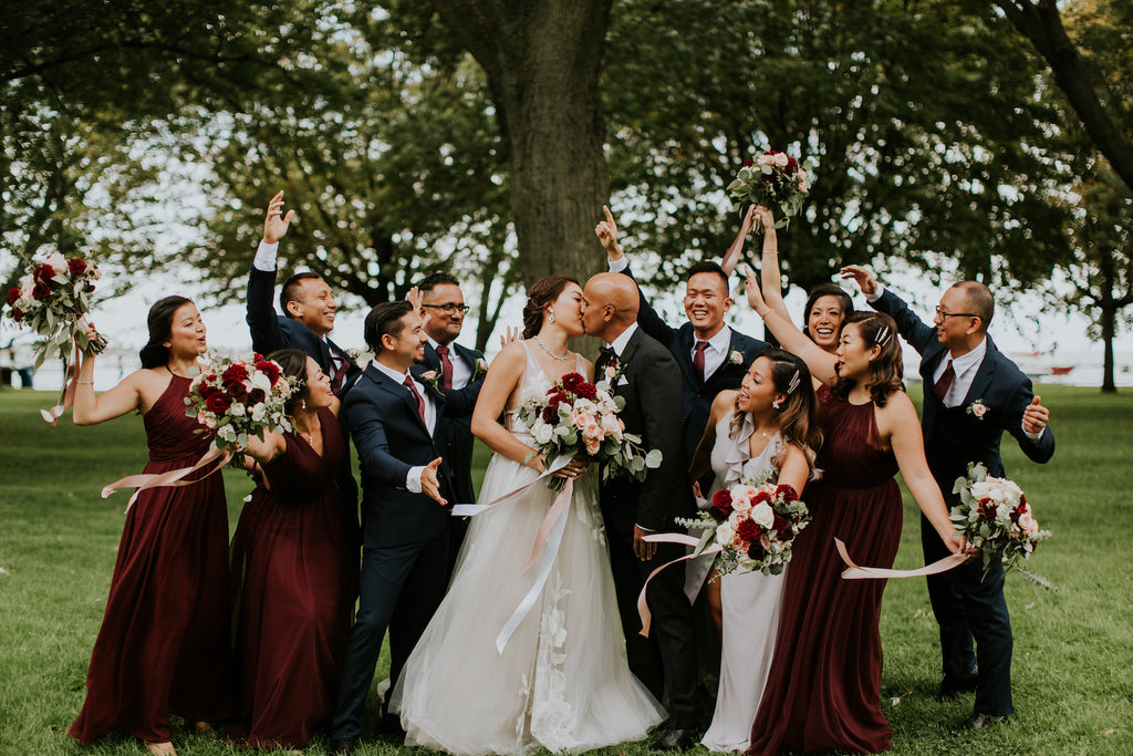 A wedding party celebrates the newlyweds while they kiss.