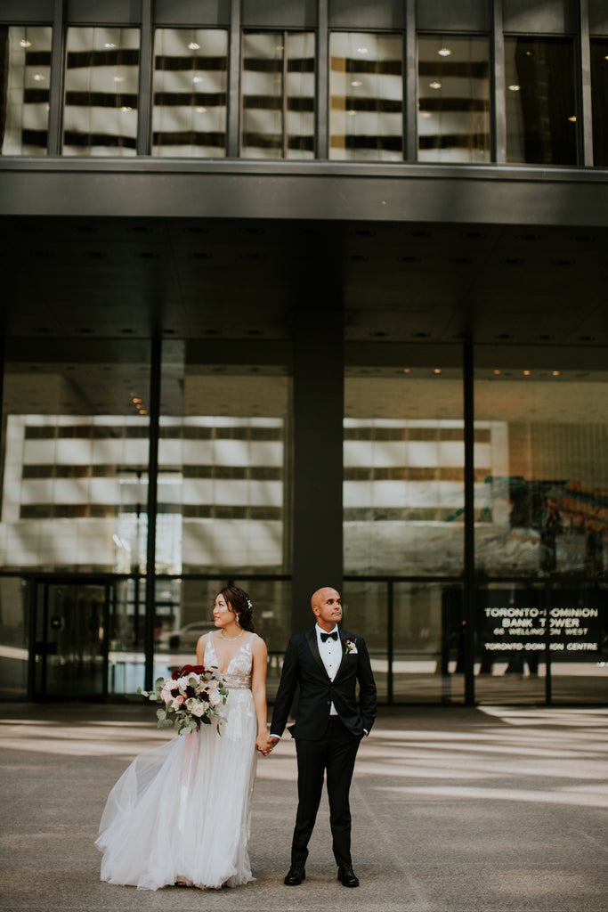 A bride and groom hold hands while walking around downtown Toronto on their big day.