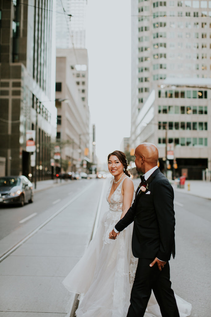 A bride and groom walk to Toronto City Hall to tie the knot.
