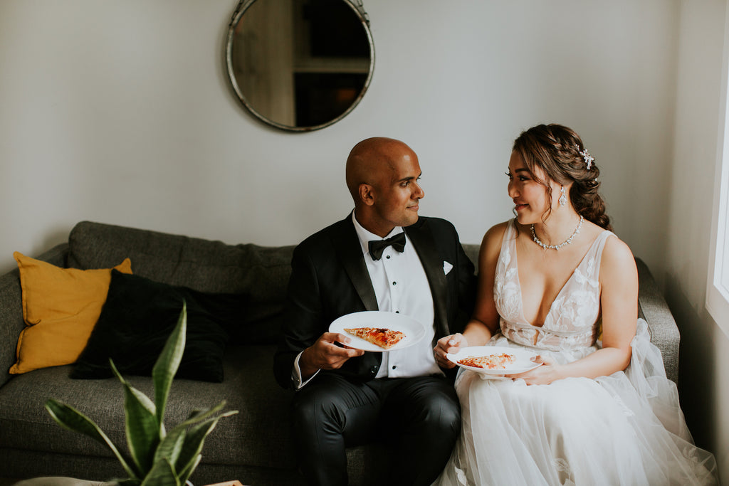 A bride and groom share a slice of pizza.