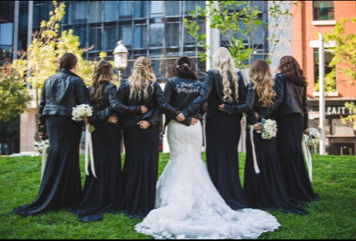 A bride and her bridesmaids pose for a photo.
