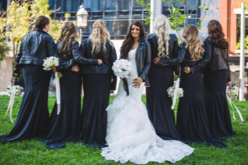 A bride smiles at the camera with her bridesmaids by her side.