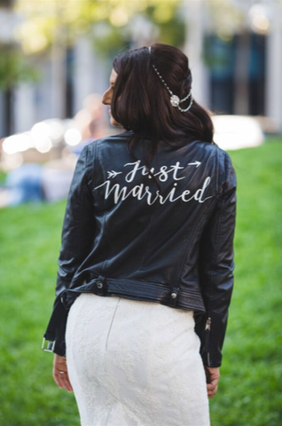 An edgy bride shows off her Just Married leather jacket.