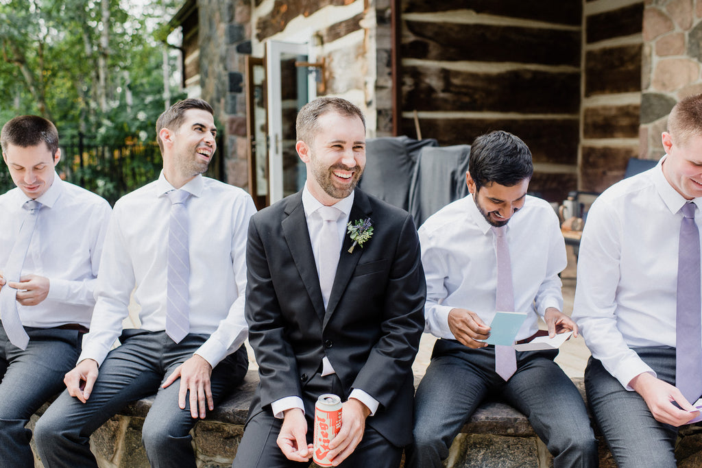 The groom and his groomsmen sit together before going to the reception.