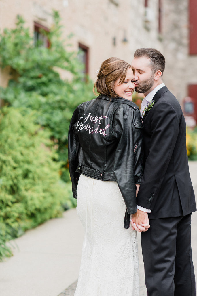 A bride shows off her just married jacket.