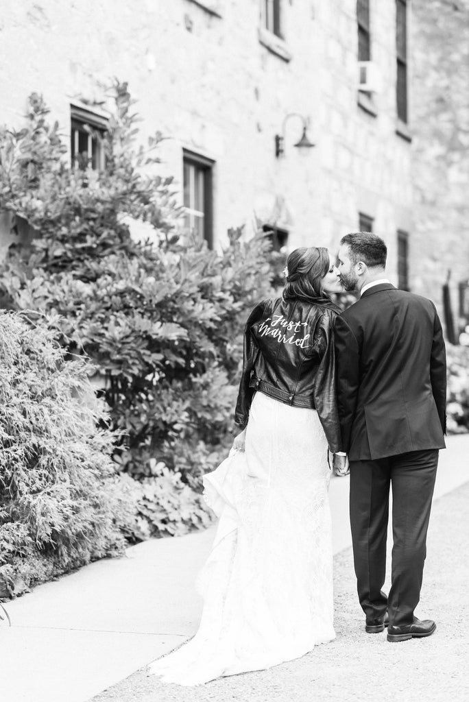 A newlywed couple walks together and shares a kiss.