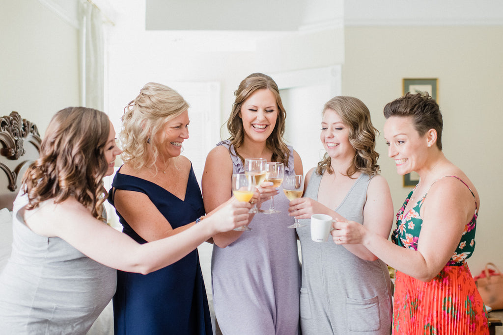 The bride and her bridal party sharing mimosas while getting ready for the big day.