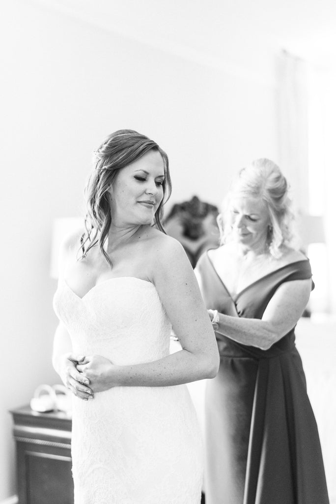 The mother of the bride helps her get her wedding gown on.