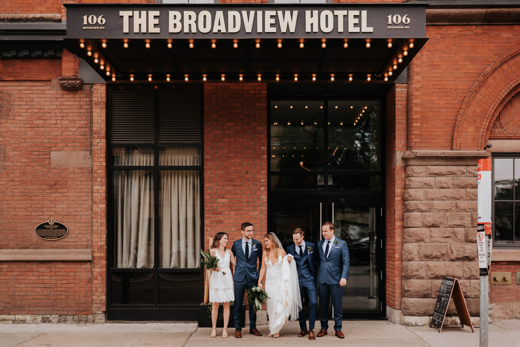 A wedding party in an intimate Toronto wedding stands outside the Broadview Hotel.