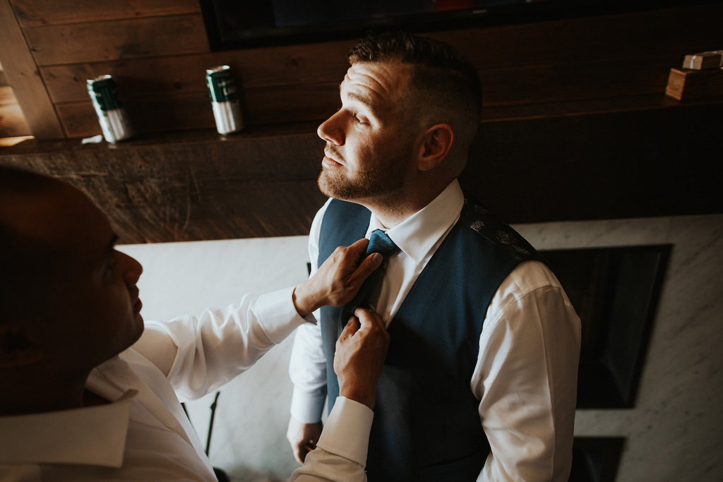 A groomsmen adjusts the grooms tie.