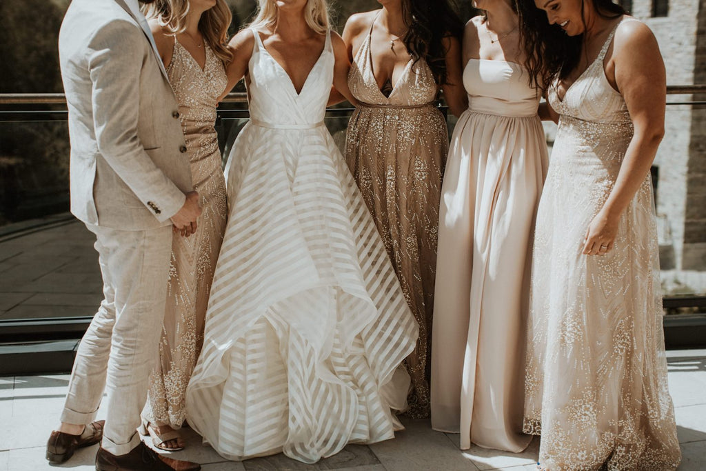 A bridal party wearing neutral beige and blush tones poses for a picture.