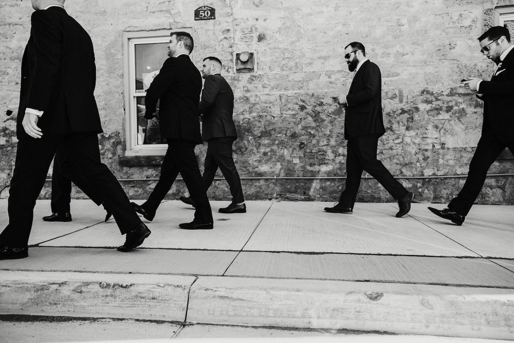 The groom and his groomsmen walk to the wedding.